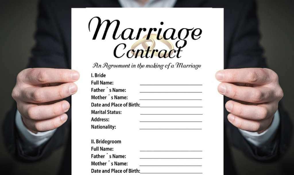 На фото мужчина держит в руках брачный договор.