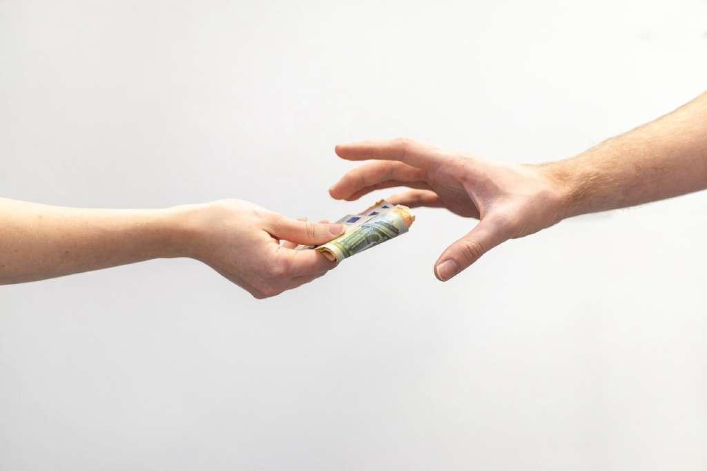 На фото один человек передает другому деньги.
