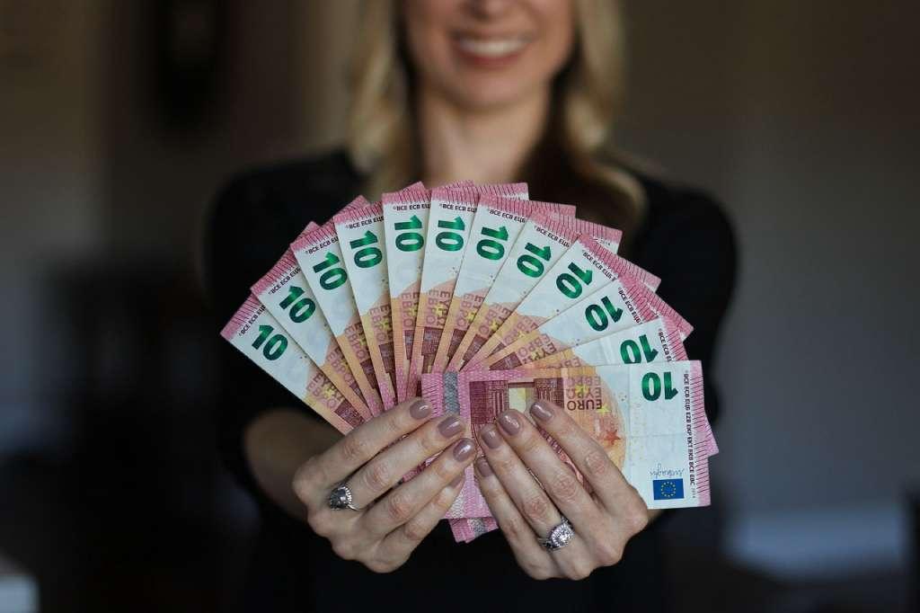 На фото девушка держит деньги в руках.