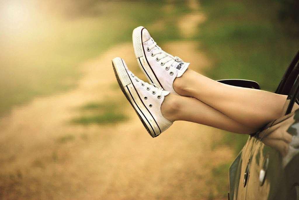 На фото ноги девушки выглядывают из автомобиля.