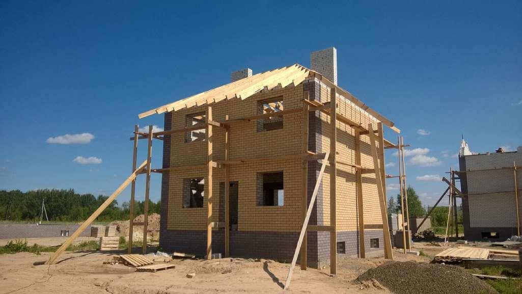 На фото изображен дом, который строится.