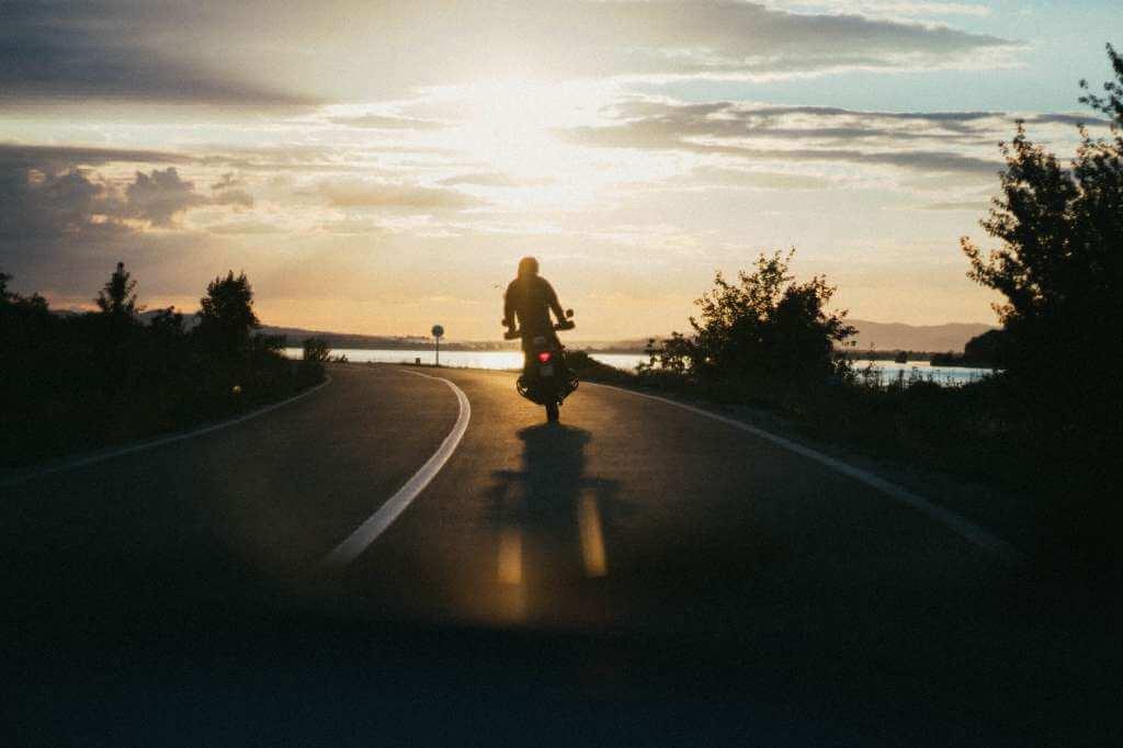 На фото человек едет по дороге на мотоцикле.