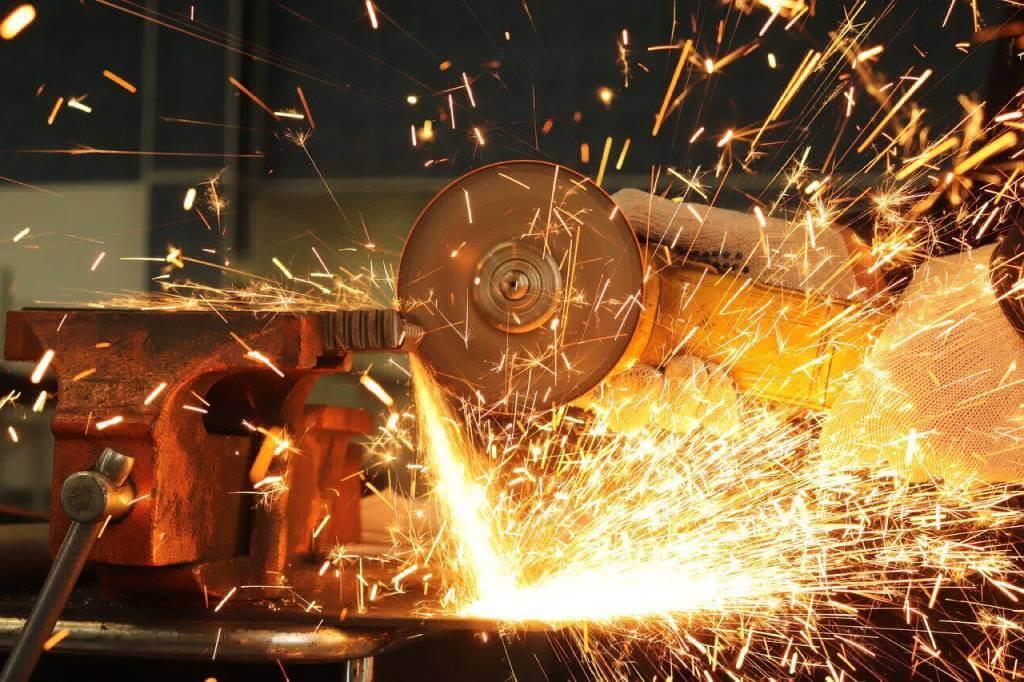 На фото работник режет металл.