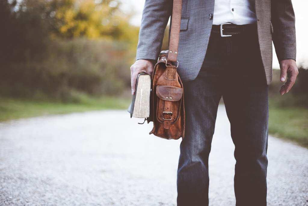 На фото учитель с портфелем и книгой.