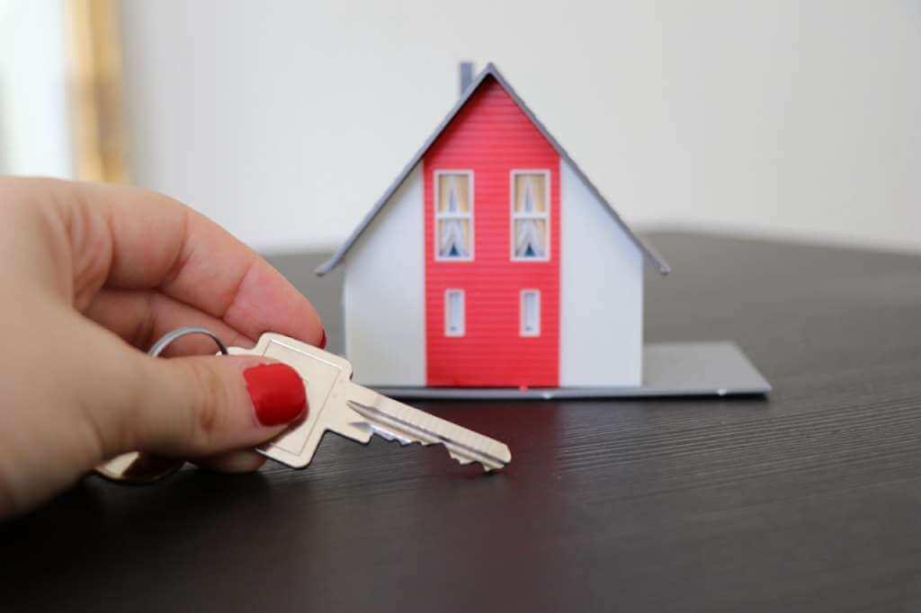 На фото девушка держит в руке ключ от дома.