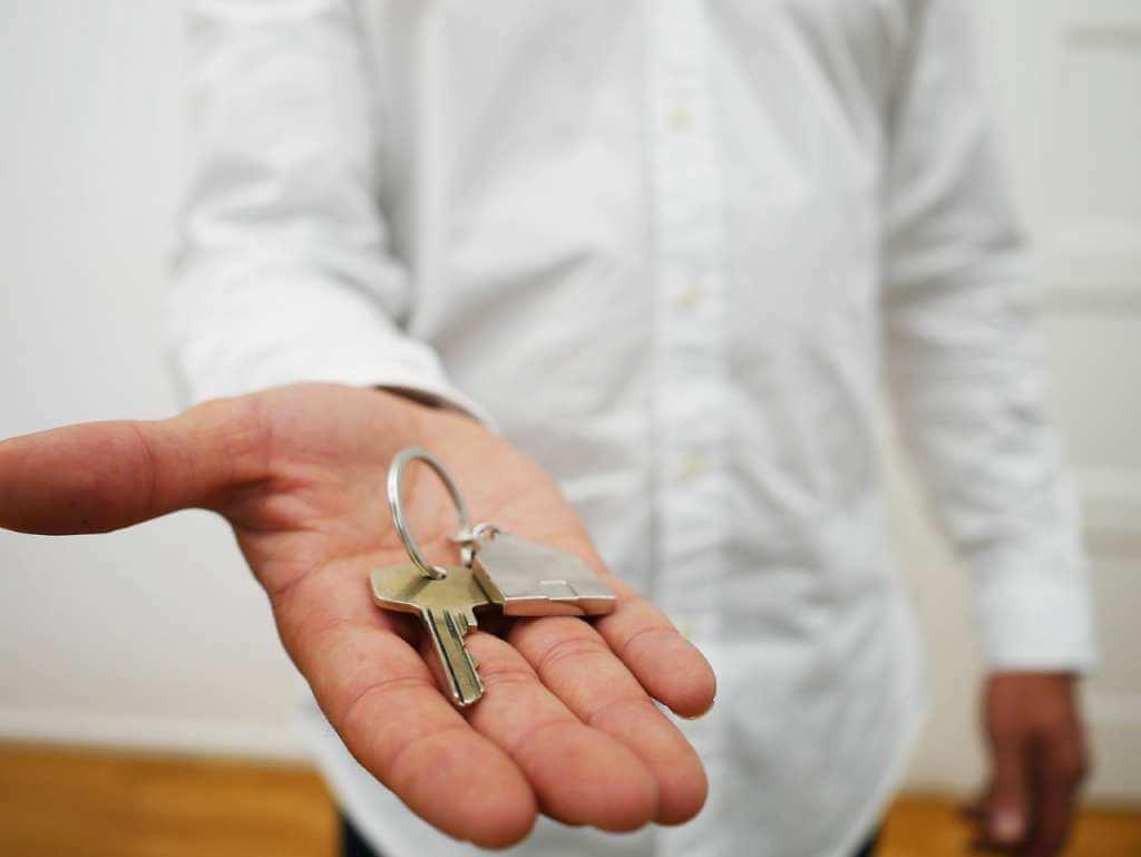 На фото мужчина предлагает ключи от дома.