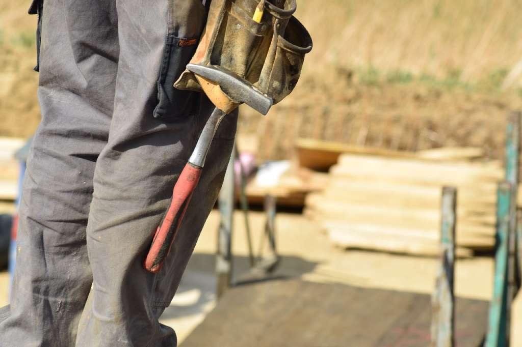 На фото изображен строитель с инструментом.