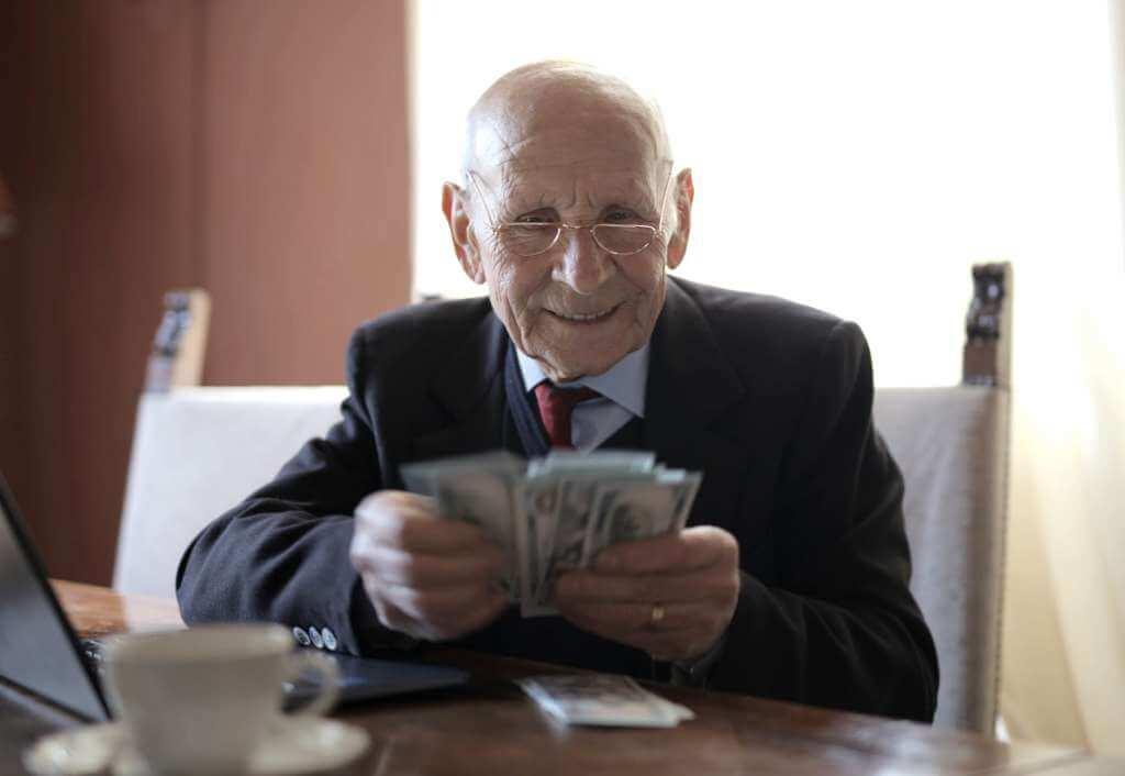 На фото мужчина считает деньги.