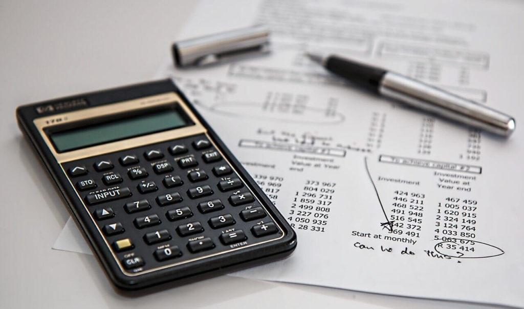 На фото изображен калькулятор, ручка и бумага.