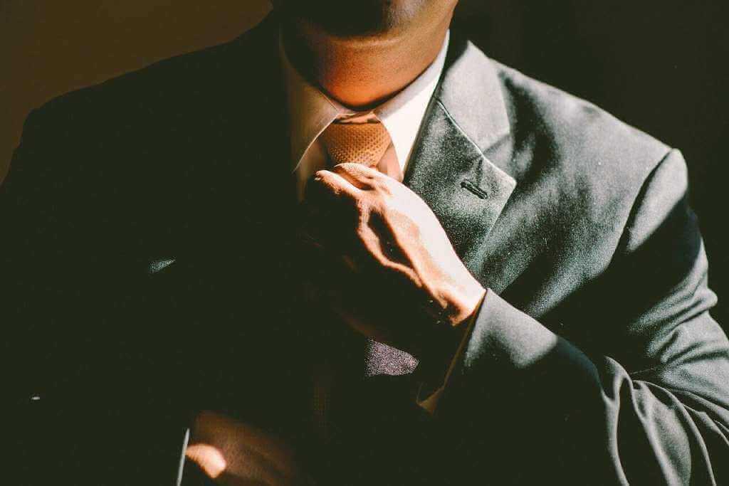 На фото работник поправляет галстук.