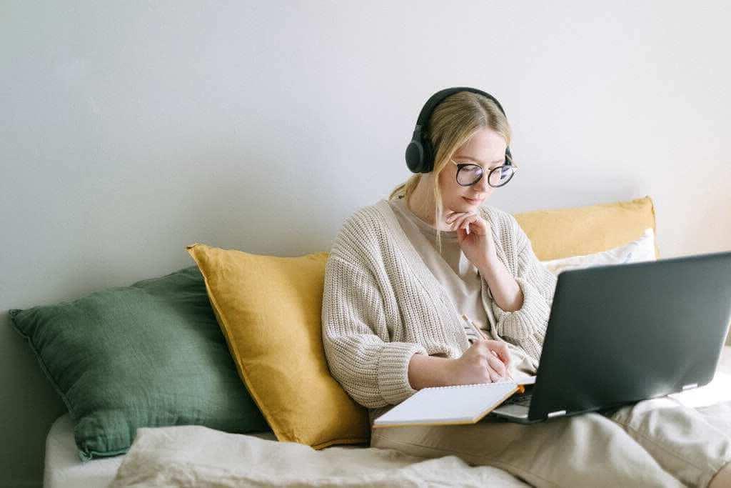 На фото девушка сидит на диване и работает дистанционно.