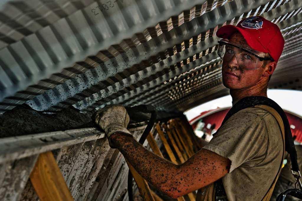 На фото строитель выполняет свою работу.