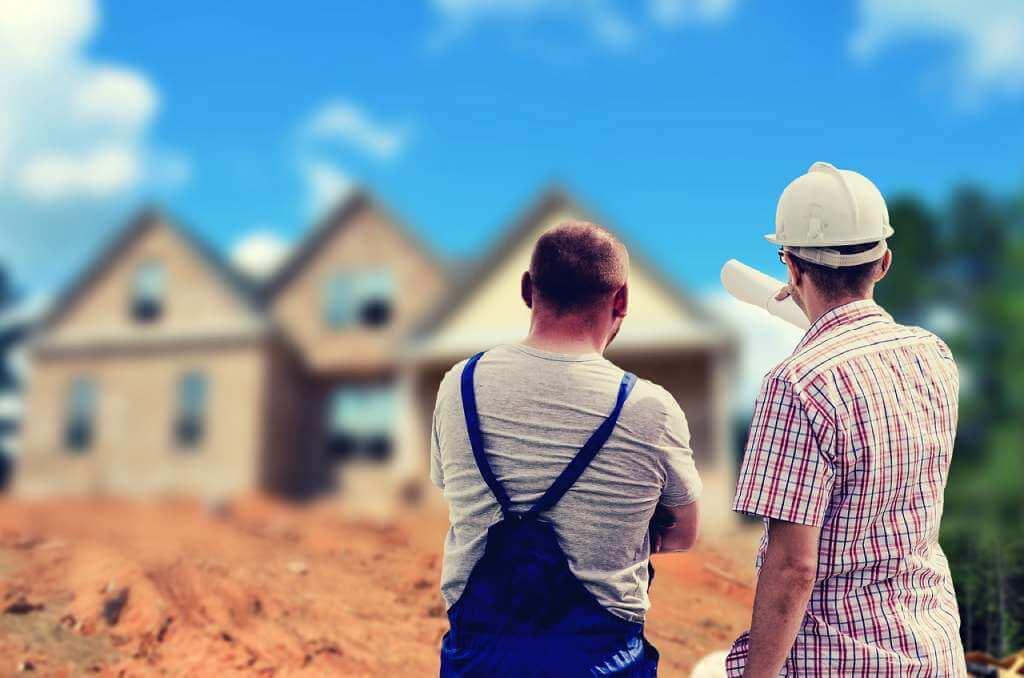 На фото строители смотрят на дом.