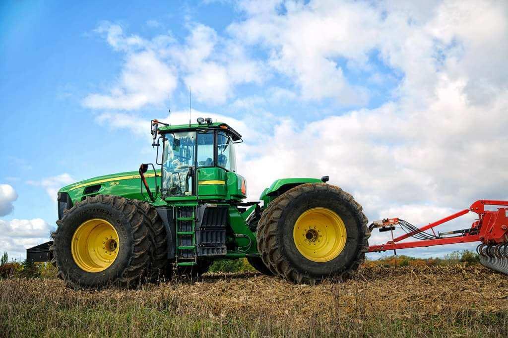 На фото изображен трактор на поле.