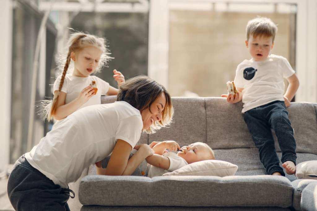 На фото мать играет с детьми в квартире.