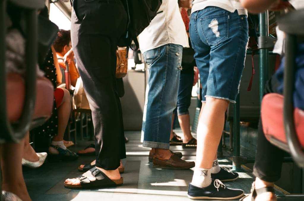На фото изображены пассажиры внутри общественного транспорта.