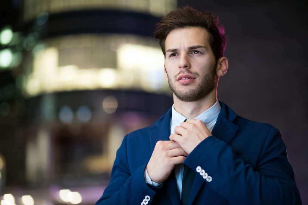 На фото мужчина поправляет галстук.